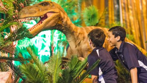 """""""Two young boys are touching the claw of an animatronic dinosaur."""""""