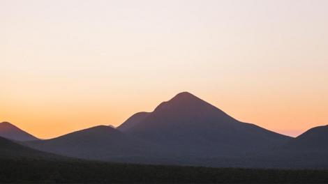 """""""A photograph of a mountain with the sun rising behind it."""""""