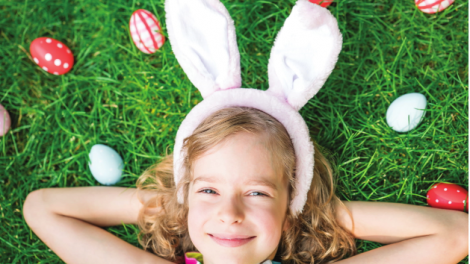 A smiling child relaxes on a lawn dotted with colourful Easter eggs