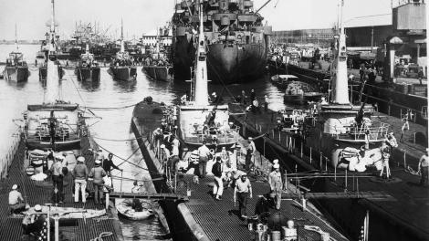 Black and white image of submarines and ships in dock