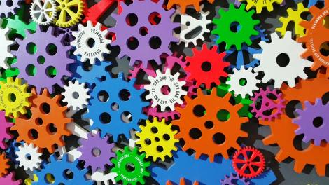 A stack of small, brightly colourful cogs