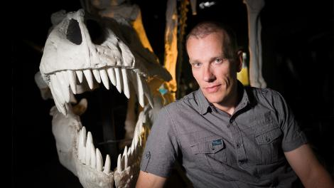 A scientist standing next to a T-Rex skull