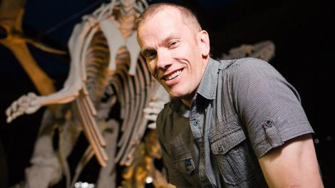 Dr Mikael Siversson standing alongside a dinosaur cast