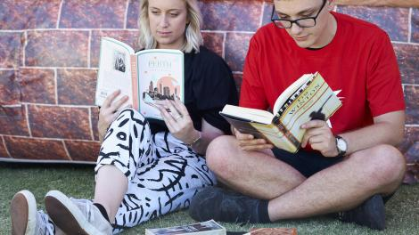 A man and woman reading books about Western Australia