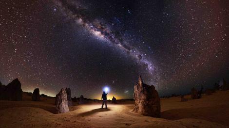 Man standing under night sky at Nambung National Park.