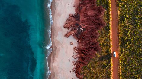 Ocean, red dirt and car driving along a dusty road - aerial shot.