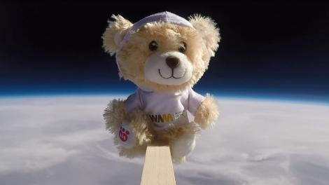 Nugget the teddy bear floating above the curvature of the Earth