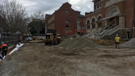 Heritage buildings in the background, dirt that has been levelled in the foreground