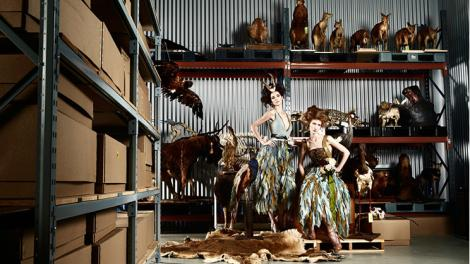 Two models posing near some taxidermied animals