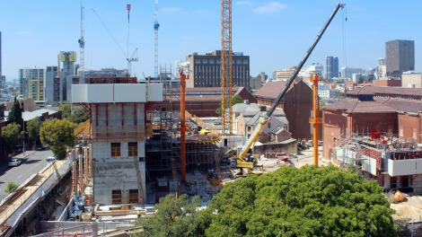 """Tree in foreground, concrete square block around three storeys high, cranes and machinery moving and lifting concrete."""