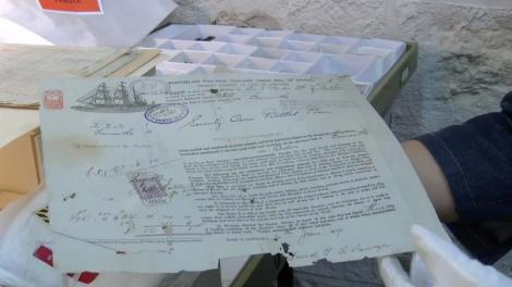 Document found in the shipwreck of the Sepia being held by white gloves