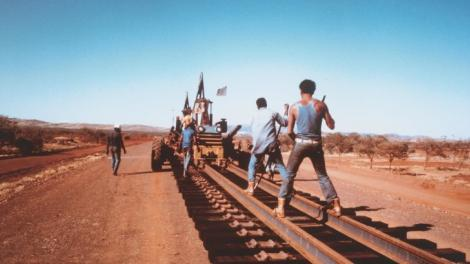 """A group of men laying track in the hot sun."""