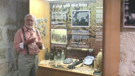 Patrick Baker with a cabinet containing items from the James Mathews Shipwreck