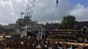 A large drill lays horizontally on the ground, a crane in the background and heritage buildings
