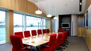 Sixteen red chairs around a boardroom table with views of the harbour through windows on one side