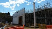 A concrete wall stands at the background of the photo. A pole is in the foreground.  Scaffold is holding up the structure.