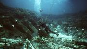 Diver inspecting objects at shipwreck site