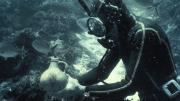 Person underwater in diving suit holding an object