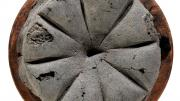 """A round black loaf of carbonised bread. It had been marked to be cut into eight triangles."""