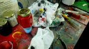 Image of a table covered in paints, syringes, cloths and other tools used for colouring badges.