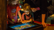 """""""A child is aided by their parent to operate a digital screen."""""""