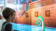 """""""A young boy looking with awe at a digital screen that has a cartoon of a pirate ship and giant squid on it."""""""