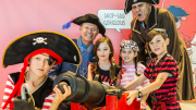 """""""A group of children and adults dressed as pirates, posing around a canon."""""""