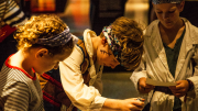 """""""A group of children dressed as pirates operating a mechanical stamp within the exhibition."""""""