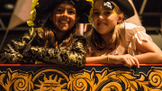 """""""Two girls dressed as pirates have their photo taken at the helm of a replica pirate ship."""""""
