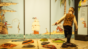 """""""A young boy walking across a plush map of a deserted island."""""""