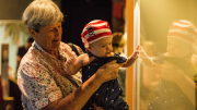 """""""An older lady holds a baby dressed as a pirate. The baby's reflection can be seen in the exhibition case's glass."""""""