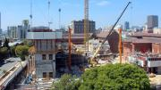 """""""Tree in foreground, concrete square block around three storeys high, cranes and machinery moving and lifting concrete."""""""