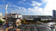 """Steel mesh laid on black flooring, concrete arm delivers wet concrete to be laid."""