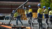 Six workers in high vis and hard hats stand waiting for concrete to pour.  Two workers holder a hose and pour the concrete into position on the ground.