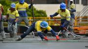 Four workers smooth our concrete for a slab.  One man is bending over and drawing a tool over the concrete to smooth it.  The other three workers are waiting to assist.