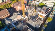 birds eye view of construction shows large crane in centre of construction site