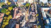 Looking down from above.  Heritage buildings are the left of the photo, a crane in the middle and construction and scaffolding materials to the right.