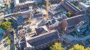 birds eye view of construction with victorian era buildings in foreground and construction of new building in background