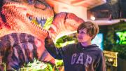 A child looking at a dinosaur in awe, while touching the dinosaur's large sharp teeth.