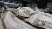 Large bones sit on pallets wrapped in plastic in a warehouse.