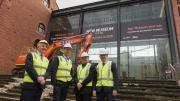 Four men in high ves vests and hard hats pose for a photo in front of the foyer of the WA Museum.  A small construction machine with a crane arm is behind them ready to smash the glass foyer.