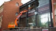 An orange construction machine with a crane arm taps the glass of the foyer which is smashing.