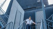 A submarine tour guide standing at the entrance of the HMAS Ovens.