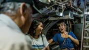 Two visitors laughing as their HMAS Ovens tour guide regales them with stories.