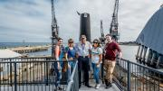 A tour group stand for a photo in front of the HMAS Ovens.