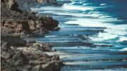 A rugged coastline with waves breaking on the shoreline