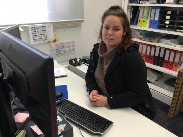 Caitlin Bonfield sitting at her desk