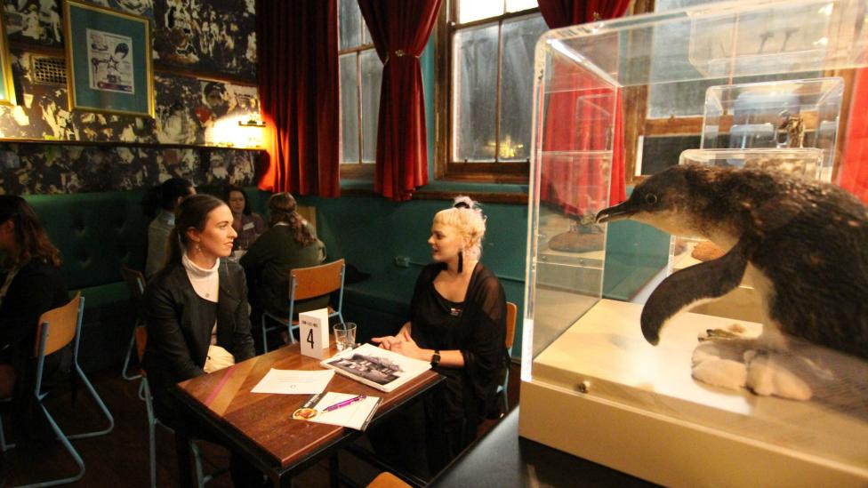 """Two young women talking at a table, taxidermied penguin in a perspex case in the foreground."""