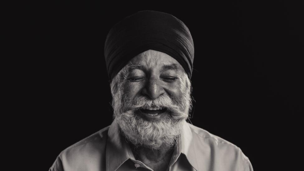 """Man with silver beard wearing turban laughs, his eyes are closed."""