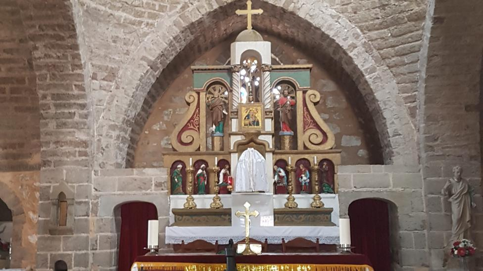 """""""Chapel with religious cross and alter with yellow and white fabric within a stone building."""""""